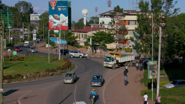 traffic & pedestrians at langata rd & gandhi ave roundabout nairobi  kenya  africa - banner sign stock videos & royalty-free footage