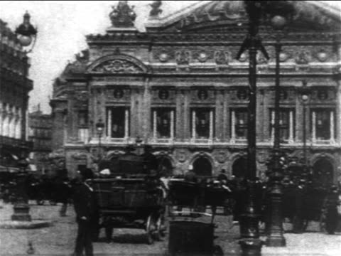 stockvideo's en b-roll-footage met b/w 1904 pan traffic + pedestrians on street outside l'opera de paris / paris - frankrijk