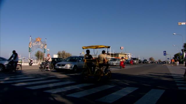 traffic, pedestrians, pedicabs pass beachfront. - fahrradtaxi stock-videos und b-roll-filmmaterial