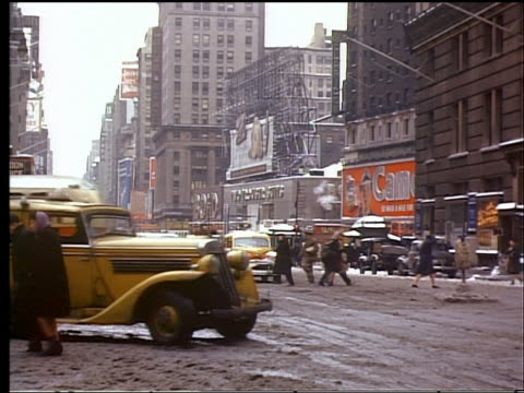 vídeos de stock e filmes b-roll de 1944 traffic + people crossing slushy street in winter at times square / new york city - 1944