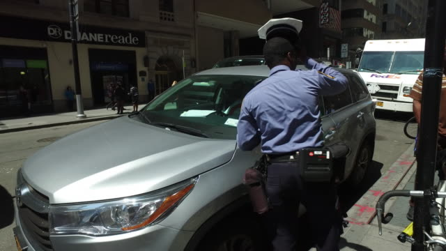 Traffic police is writing a ticket for illegal parking in New York Manhattan