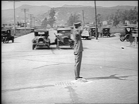 b/w 1926 traffic policeman jumping over man (harry langdon) stretched between two moving cars - 1926 stock videos & royalty-free footage