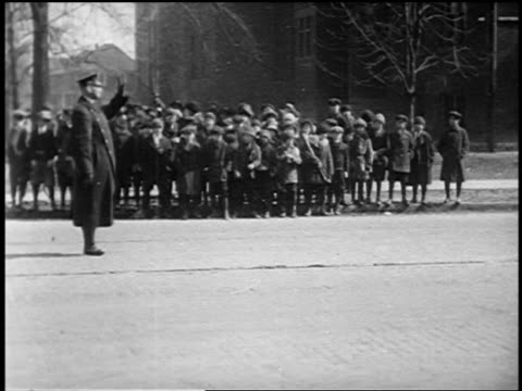 b/w 1920 traffic policeman waving crowd of running children across street after car passes - school child stock videos & royalty-free footage