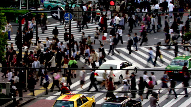 Traffic pulls through an intersection after pedestrians cross the street. Available in HD.