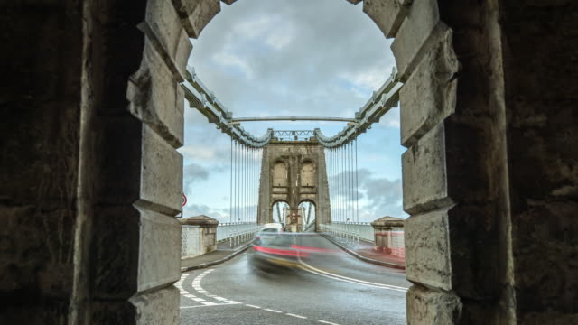 traffic rapidly passes an arch at the south end of the menai suspension bridge linking anglesey and wales - wales stock videos & royalty-free footage