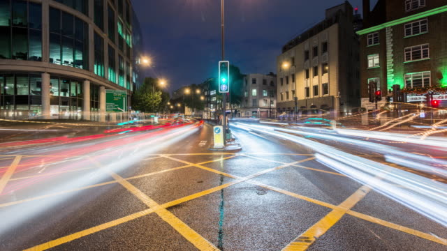 vídeos de stock e filmes b-roll de traffic rapidly streams past a yellow box junction on the euston road in north london on a wet rainy evening - marca de estrada