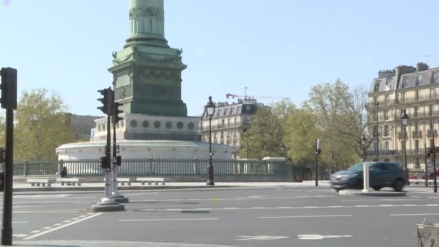 traffic reduced to the bare essentials and just a few passersby on the streets paris's place de la bastille usually bustling with traffic and... - bastille paris stock videos & royalty-free footage