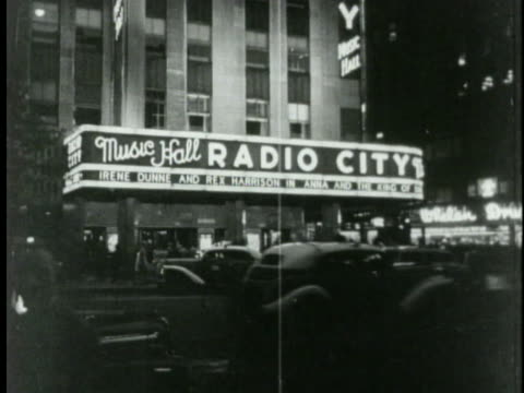 traffic rolls by the radio city music hall on new york's sixth avenue. - radio city music hall stock videos & royalty-free footage