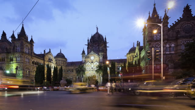 tl, ws traffic rushes past victoria terminus railway station at dusk / mumbai, india - chaos stock videos & royalty-free footage