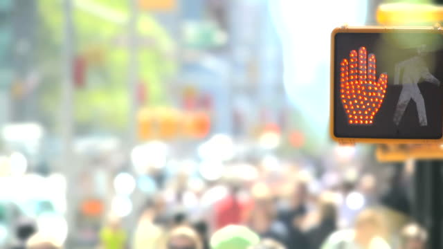 Traffic Sign and Blurred Crowds of People Walking in New York City
