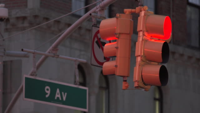 A traffic signal turns from red to green.  9th ave sign behind
