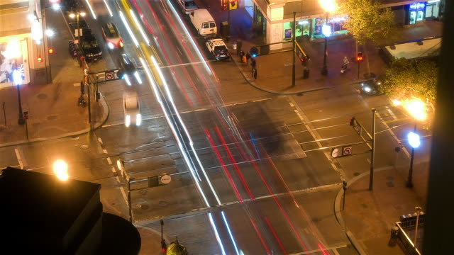 WS AERIAL PAN ZO T/L Traffic speeding through  busy intersection at night  / San Francisco, California
