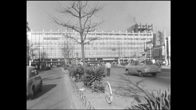 traffic speeding toward tokyo station stops for pedestrians in a crosswalk. - 1960~1969年点の映像素材/bロール