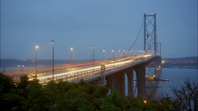 stockvideo's en b-roll-footage met traffic speeds across the forth road bridge over firth of forth. - firth of forth