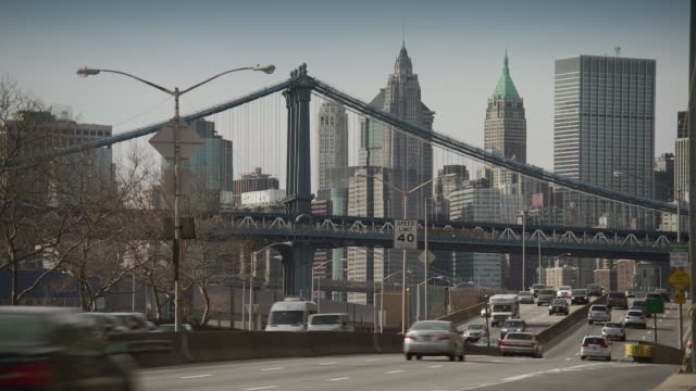 traffic speeds down the fdr highway in new york city the manhattan bridge and the downtown skyline are featured. - bare tree stock videos & royalty-free footage