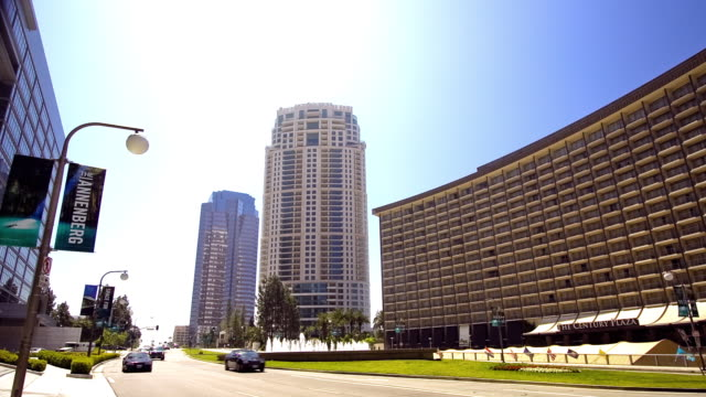 traffic speeds past the century plaza hotel and fox plaza on the avenue of the stars in los angeles. - century city stock-videos und b-roll-filmmaterial