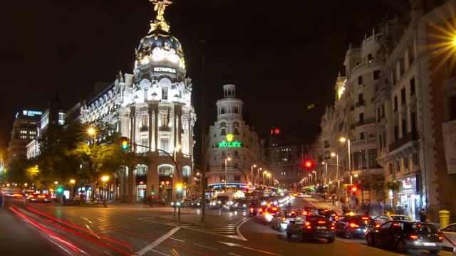 wa t/l zo traffic streaking by the edificio metropolis at night/madrid, spain - マドリード グランヴィア通り点の映像素材/bロール