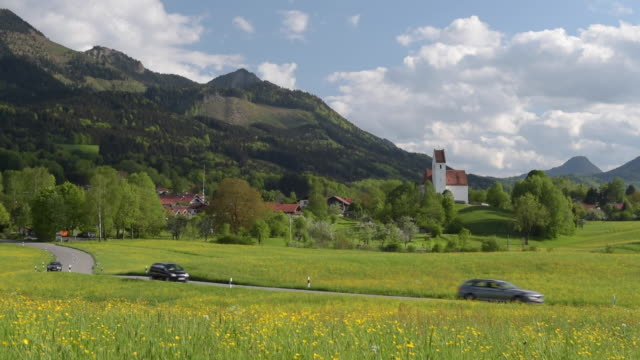 Traffic through buttercup meadow and church at Chiemgauer alps