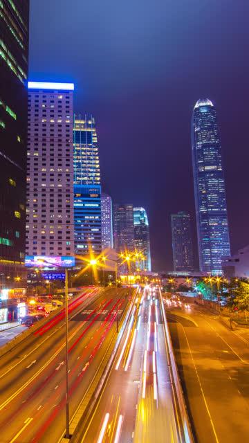 (Vertikal) Time-Lapse-Verkehr und Hongkong Wolkenkratzer Stadtbild in der Nachtzeit.
