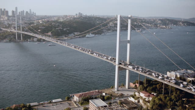 aerial traffic traveling across a suspension bridge spanning the bosphorus strait / istanbul, turkey - july 15 martyrs' bridge stock videos & royalty-free footage