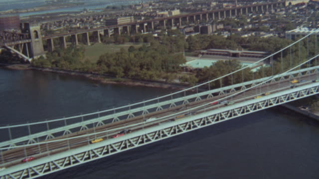 1973 MONTAGE Traffic traveling along the Verrazzano-Narrows bridge and the New York City skyline / Brooklyn, New York, United States
