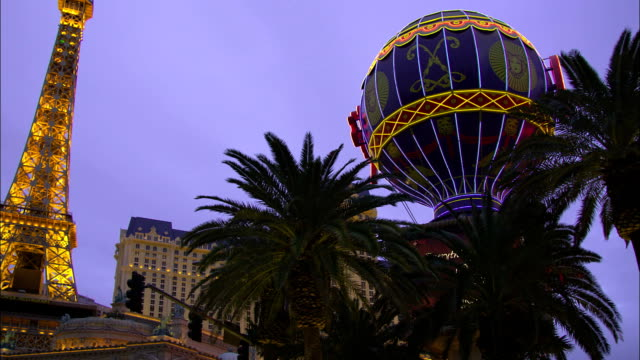 traffic travels along a street in front of the paris in las vegas, nevada. - paris las vegas stock videos & royalty-free footage
