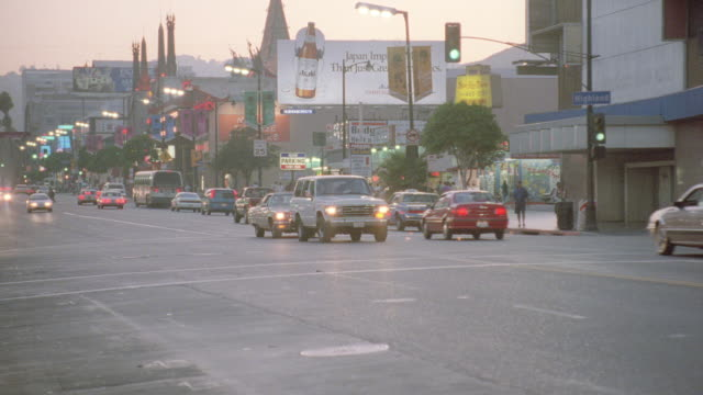vidéos et rushes de traffic travels along hollywood boulevard past grauman's chinese theatre near highland avenue. - hollywood boulevard