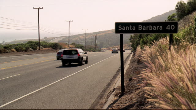 traffic travels along the pacific coast highway past a road sign announcing santa barbara 40 miles. - santa barbara bildbanksvideor och videomaterial från bakom kulisserna