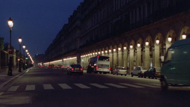 vidéos et rushes de traffic travels along the rue de rivoli in paris, france. - image animée