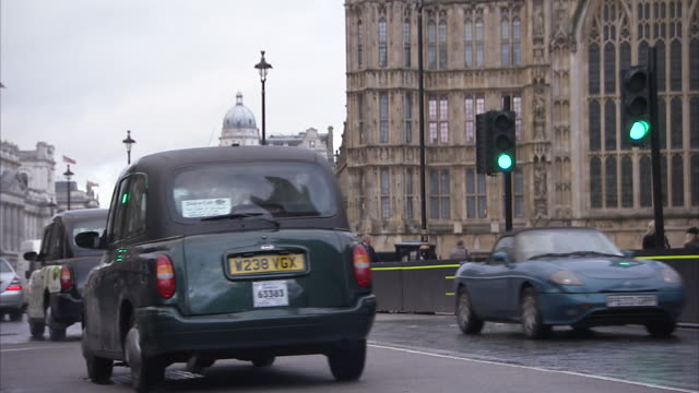 traffic travels down a busy city street near the palace of westminster in downtown london. available in hd. - bumper stock videos & royalty-free footage