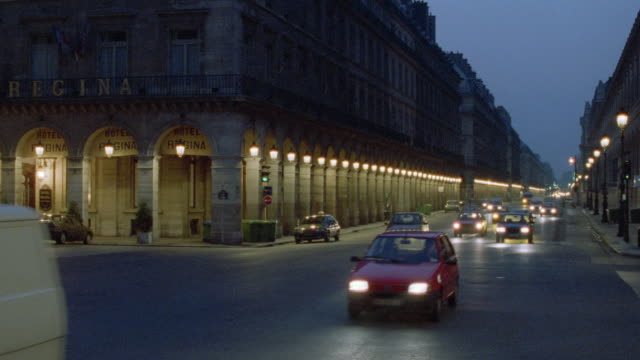 traffic travels on a busy city street beneath the historic hotel regina in paris. - 1995 stock videos & royalty-free footage