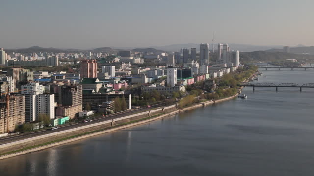 traffic travels on a highway between the taedong river and the pyongyang skyline. - north korea stock videos & royalty-free footage