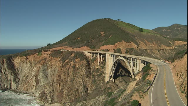 traffic travels on highway 1 across bixby creek bridge over rainbow canyon in big sur, california. - route 001 stock videos & royalty-free footage