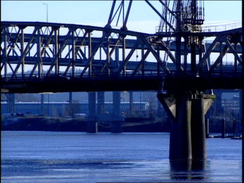 vídeos y material grabado en eventos de stock de traffic travels over a bridge spanning a river. - vehículo comercial terrestre