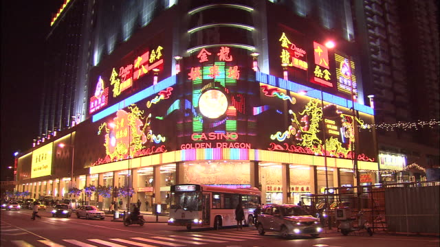 traffic travels past a casino with a huge flashing neon sign. - macao stock videos & royalty-free footage