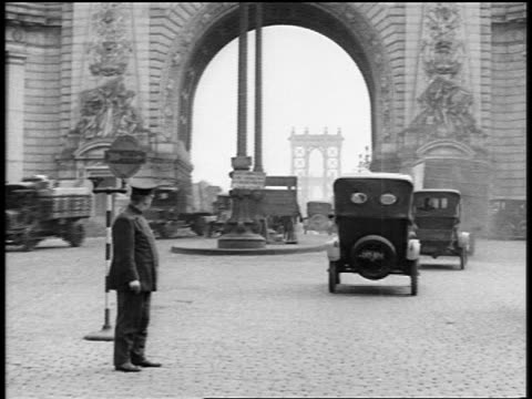 vídeos de stock e filmes b-roll de b/w 1919 traffic under arch towards manhattan bridge as policeman directs traffic in foreground / nyc / news - 1919