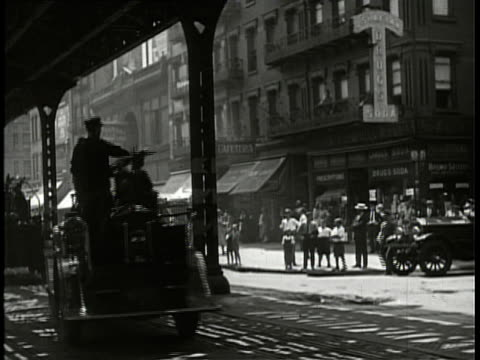 1940 b/w montage traffic under elevated train tracks, with 1920s fire engines putting out nearby fire / lower east side, new york city, new york, usa - 1940 stock videos and b-roll footage