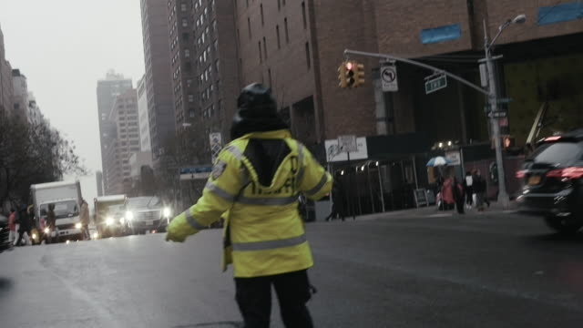 traffic warden guiding cars on city street - forze di polizia video stock e b–roll