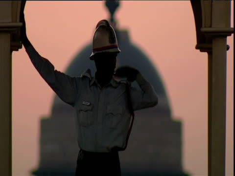 Traffic warden standing in domed gazebo directs traffic at sunrise hazy pink sky in background Delhi