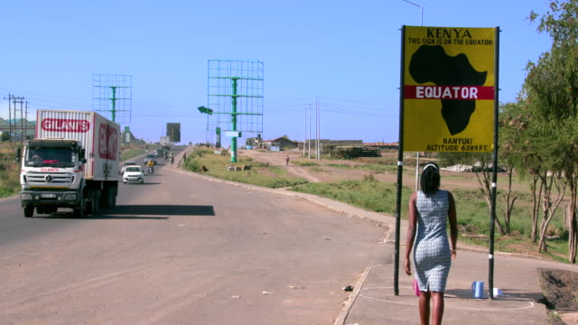 Traffic With Woman Walking To Equator Sign Nanyuki  Kenya