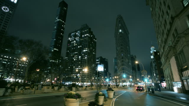 ws t/l traffic zooming onto avenue alongside the flatiron building in new york city at night / new york city, new york, usa - flatiron building manhattan stock videos and b-roll footage