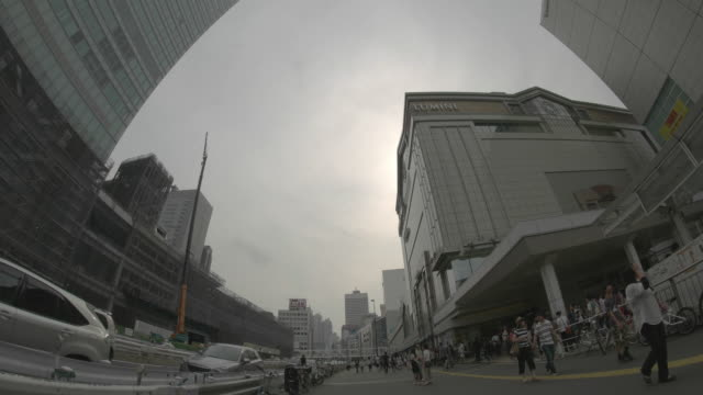 WS, Trafific and pedestrians front of the Shinjuku station.