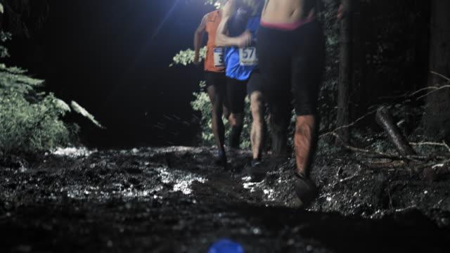 Trail run Mitbewerber Laufen auf einem schlammigen Straße bei Nacht