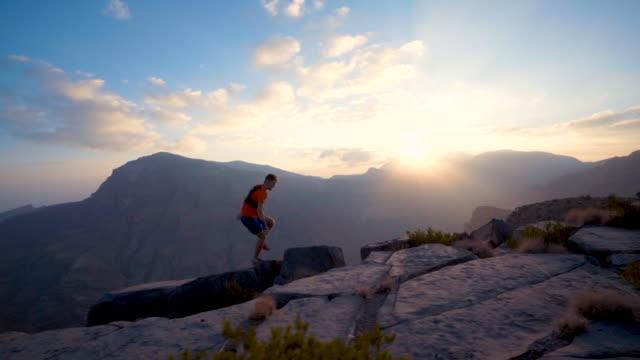vídeos de stock, filmes e b-roll de trail runner ascending rocky trail at sunrise above canyon - calções de corrida
