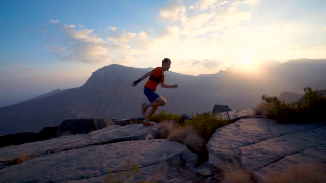 trail runner ascending rocky trail at sunrise above canyon - 避ける点の映像素材/bロール
