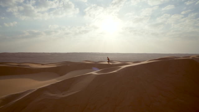 vídeos de stock e filmes b-roll de trail runner ascends dunes in desert - horizonte