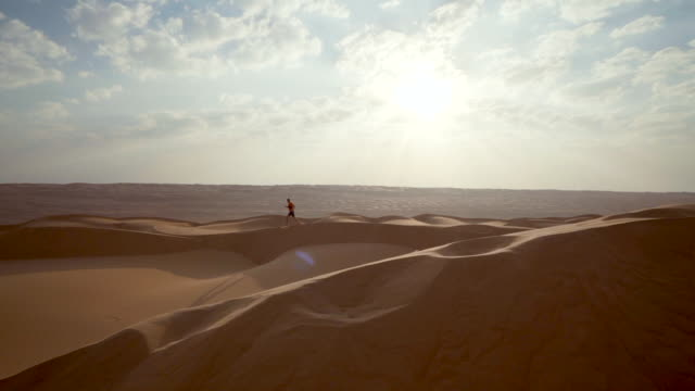 trail runner ascends dunes in desert - finding stock videos and b-roll footage