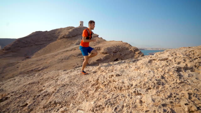 trail runner ascends rocky mountain to viewpoint over ocean - querfeldeinlauf stock-videos und b-roll-filmmaterial