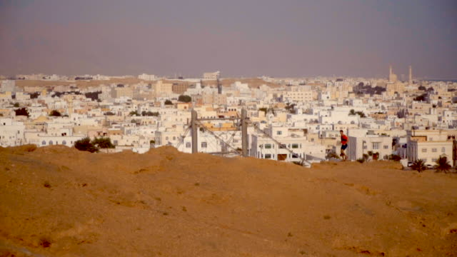 Trail runner ascends rocky trail above middle eastern town