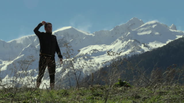 Trail runner enjoying a spectacular view in front of a snowy peaks and keeps running